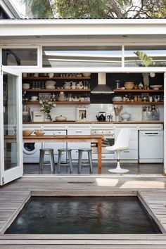 dark kitchen with wooden shelves and white cabinetry
