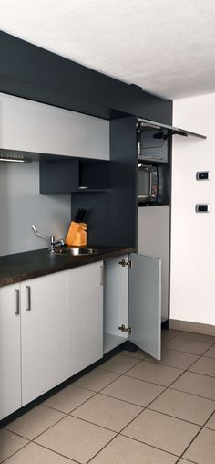 Break area furniture: doors and wall units in gray laminate. Frame sides are made of laminate anthracite color . Top panel preformed as stone . Detail of the wall unit with LED light. Column unit with microwave and recessed fridge.