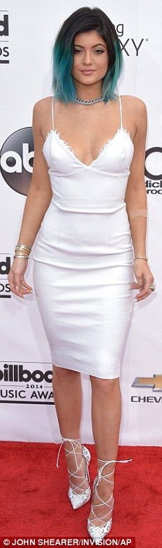 Stand-out style: Kylie Jenner, opted for a tight white midi-length frock and white leopard-print stilettos featuring a lace-up design, while she showed off her recently cropped and dip-dyed tresses featuring her natural black hue to mid-length and bright turquoise ends
