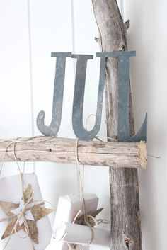 cute display idea hanging fake wrapped presents from wooden ladder or driftwood