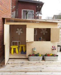 This playhouse looks like a cardboard box with cutouts which very cool. The sliver of glass just beneath the roof makes this even more interesting.