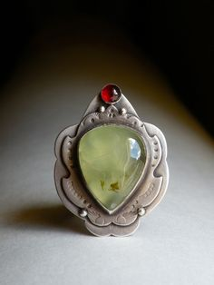 Sterling, Prehnite and Garnet ring. Prehnite is a fossil like stone of unconditional love while Garnet is a stone of bravery and passion. Garnet is also commonly known as a married couple's second year anniversary stone as well as the birthstone for the month of January.