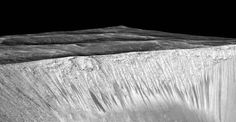"""Dark narrow streaks, called """"recurring slope lineae,"""" emanate from the walls of Garni Crater on Mars, in this view constructed from observations by the High Resolution Imaging Science Experiment (HiRISE) camera on NASA's Mars Reconnaissance Orbiter.  The dark streaks here are up to few hundred yards, or meters, long. They are hypothesized to be formed by flow of briny liquid water on Mars.  The image was produced by first creating a 3-D computer model (a digital terrain map) of the area…"""