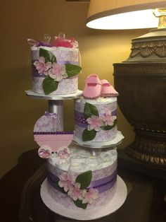 This beautiful and unique three tier baby girl diaper cake will make a perfect centerpiece or even an elegant gift for a baby shower. Its unique