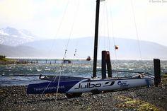 Cammas' Nacra F20 Carbon FCS on the shore of Seno Lauta Harbour. Full carbon racing machine - carbon hulls, mast, rudders, and foils.