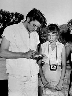 Elvis Presley signing autographs for his fans, circa 1957.