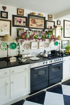 the kitchen walls are covered with lots of botanical prints in black frames