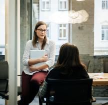 Two businesswomen in a modern office are discussing something in a meeting. One of them is seen from behind sitting on a chair while the other one is leaning on a table while holding her laptop.
