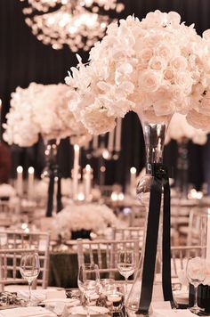 Modern floral arrangements of white roses and orchids are placed in glass floral vessels accented by sophisticated black sashes.