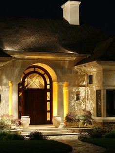 """Dramatic Doors To generate a sense of drama for the front door of this house, which is set in a very narrow porch, Mitchell of NiteLiters chose to backlight the pillars instead of spotlight them. """"It creates depth and leads your eye past the pillars to what's behind them,"""" he says. An amber lens makes the dark wood of the door look even richer."""