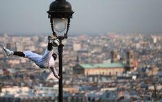 Ein Fußball-Freestyle-Artist demonstriert auf dem Montmartre in Paris neben der Basilika Sacré-Cœur seine Körperbeherrschung an einer Laternenstange. (Paris, Frankreich, von Christian Hartmann/Reuters, publiziert am 8. November 2012)