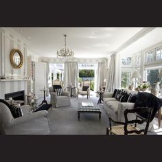 Painted grey and white stripes accentuate the monochromatic interiors in the formal living room. The architect added a bay window in the original style of the house to let in more light.