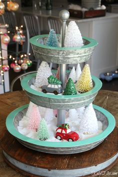 LOVE this tiered tray filled with bottle brush trees and mini cars carrying Christmas trees kellyelko.com