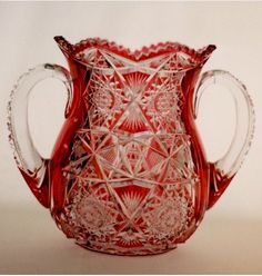 ACGA American Brilliant Cut Glass Examples Cranberry-to-Clear 2-Handled Loving Cup. 7in. tall x 9in. diameter (handle-to-handle). Signed: Hawkes. A 24-point hobstar is cut on the bottom of this loving cup. The sides are cut in two 16-point hobstars at the top and two 18-point hobstars at the bottom separated by cross-hatching, small hobstars, and fans. Cross-hatching, pyramidal diamonds, small hobstars, and zipper cutting are cut on the handles.