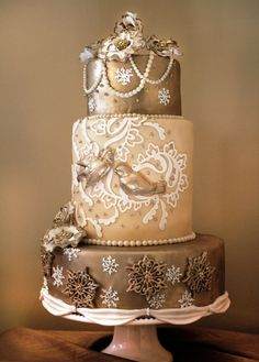 Stunning bronze and gold wedding cake with pearls, birds, and snowflakes