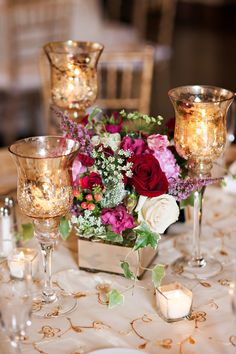Downtown Detroit wedding: elegant reception centerpiece with roses, a mix of other romantic flower favorites, and gold mercury glass candleholders. Flowers: vivianoweddings.com | Photography: czapstudios.com