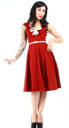 The Heidi dress is a modern adaptation of the classic 50's swing dress. With a full skirt and stretch sateen fabric it hugs curves and shows just the right amount of leg. The gathering on the bust and straps along with cream piping and bow adds flattering detail to this hot number. It also comes with a matching cream belt for that perfect pinup waistline. Pair with a petticoat for an extra full skirt.