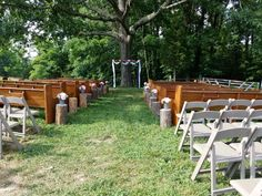 Light brown arbor with white material and floral arrangement pews and chairs with stumps and gray mason jars with flowers in them.