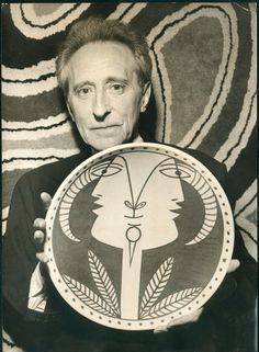 Jean Cocteau holding one of his large ceramic plates.