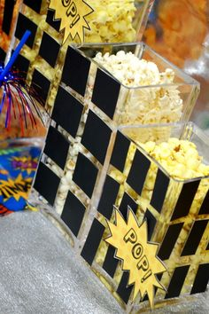 """For a Superhero Party...take plastic or glass rectangular canisters, make """"windows"""" out of black duct tape, and you have a city scape! Then fill them with """"Pop!"""" corn and other snacks. Love it!"""