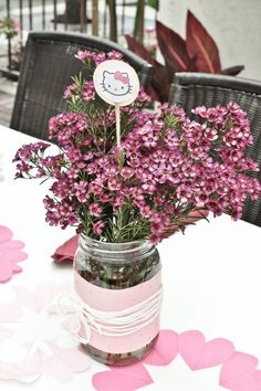 Simple DIY wedding flower centerpiece with pink wax flowers in mason jar