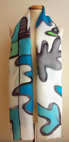 Add some wearable art to your outfit this season! This is a beautiful hand painted silk scarf. This unique asbtract design is in some shades of grey, blue, green and white colors. This will look great on you with any outfit, perfect for everyday wear or an elegant party or wedding. Size: