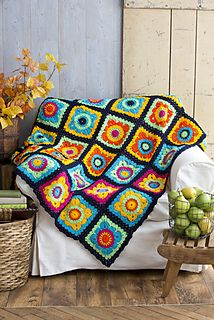 The multicolored neon circle-to-square motifs that make up this modified granny square blanket are worked in the round. For this portable project, motifs are crocheted separately, then joined piece by piece at the end.