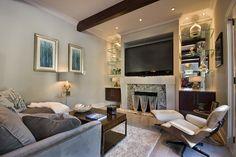 tv over fireplace, mirrored back shelving, lights, ceiling beam
