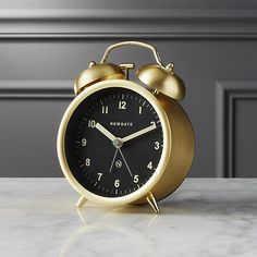 Shop charlie gold alarm clock.   Rise and shine with this modern take on an old-school wake up call.  Made in England by Newgate, brushed gold finish juxtaposes a black face with white numbers perched on two tiny angled legs.