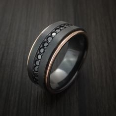 This 9mm Black Zirconium band has a BEAD BLAST FINISH. The ring has 14K Rose Gold edges that have a POLISH finish. Set into the ring are 16 beautiful Black Diam