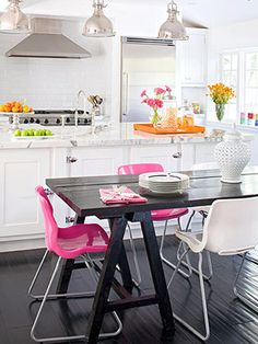 White kitchen, dark table, pink chairs, industrial lighting