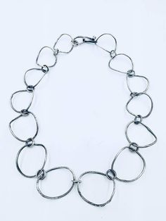 "My favorite challenge is to design and fabricate sterling silver chain. Here is a beautiful statement piece to treasure forever! Organic loops that are formed into gently bending arcs circle the neck with a beautiful hand wrought clasp. The chain measures 21"" long and is oxidised"