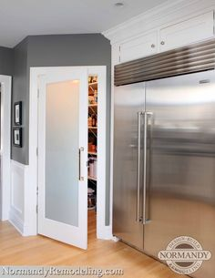 A frosted pantry door adds a stylish element to this gray and white kitchen by Normandy Remodeling's Stephanie Bryant.
