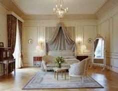 Habitación doble, de colores claros, amplia cama, gran ventanal, espejo de adorno y otras figuras y alfombra debajo de los sillones.