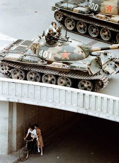 June 5, 1989, a young couple waits beneath Jianguomenwai Bridge on the fringe of Beijing's diplomatic area, as PLA tanks roll above them.