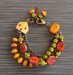 This multi-strand brass bracelet features ceramic, Lampwork, and Czech glass beads in colors of orange, green, and goldenrod yellow.  Two strands