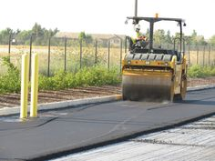The first roller passes leave marks in the fresh asphalt mat, which disappear with additional rolling and compaction as the mat cools. This is a parking lot paving operation in West Sacramento, Calif.
