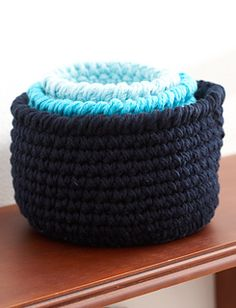 Three sizes, three shades, and infinite uses! These stout little baskets will help you out in every room of the house. (Yarnspirations)