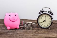piggy bank with coin stacks and alarm clock