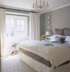 Gray carpet ve this, natural daylight in a bedroom is so relaxing!  Photographer: Margaret Mulligan  Products: Carpet, Dominion Rug; bedding, Au line Linens; chandelier, The Home Depot; wall colour, Silverado (SW 1005) Sherwin-Williams.