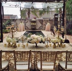 Gold sequin lace covered the rustic wood table, gold mercury housed lush white florals, while gold candelabras and festoon lighting twinkled all night long! So glam! #tyingtheknotweddings #neworleanswedding #goldwedding For more weddings or to contact us please visit us at www.tyingtheknotweddingcoordination.com