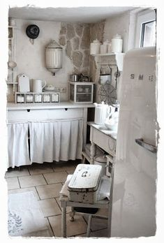 This clever hideaway curtain keeps mess tidily hidden away and adds a nice soft touch to the shabby chic kitchen. I love the white theme of this kitchen which has been achieved by painting up and aging old wood furniture (the chair, side unit, table, wall units etc).