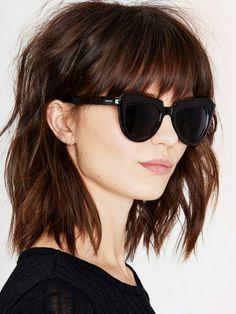Mittellange Pony Frisur, glatte kastanienbraune Haare, rosafarbene Lippen, dunkle Sonnenbrille