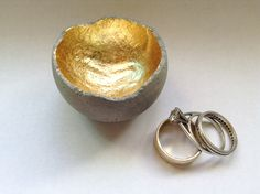 "Tiny concrete ring dish with gold inside: Small bowl measuring just over 1-1/2"" across the top made of cast concrete. The inside is coated with gold colored bronze leaf and a coat of lacquer for a shiny, smooth feel. Also available in silver or copper leaf. The outside is an uncoated matte finish. ($15.00)"