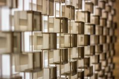 A 9 meters high sculptural installation consisting of thousands of bronze-finish boxes suspended in the atrium of the world famous Kempinski Hotel in Dubai. Designed by Giles Miller