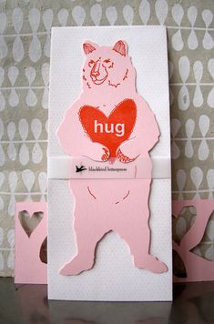 "By Blackbird Press, available at the Craft Alliance Delmar Gallery Shop. ""What better way to say ""be my valentine"" but with a bear hug. The Grizzly Bear is the largest predator in Yellowstone. She's feared, celebrated, and once fed at the dump. This card is our homage to this beautiful creature. Her little arms are ready to fill with a note, some cash, a sweet photo, or a flower. Tell someone how much you love them or share the latest picture of your new baby."""