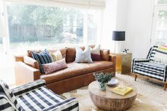 Living room with leather sofa, layered rugs and buffalo check chairs || Studio McGee