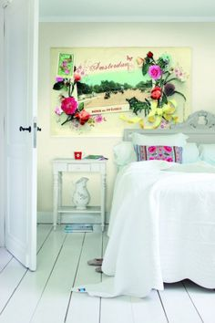 all white bedroom with pop of color in the art.
