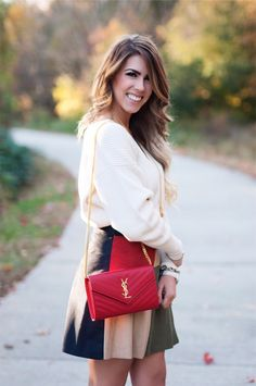 color block skirt, color block, tory burch riding boots, red ysl purse, red wallet on a chain ysl purse, free people white sweater, winter fashion, holiday outfit inspo, holiday fashion, what to wear during the holidays, suede skirt