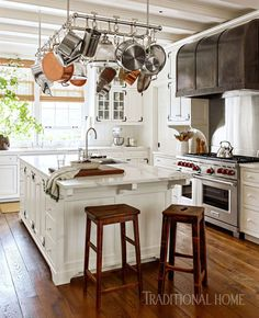 A HISTORICALY INSPIRED DUTCH COLONIAL BY GIL SCHAFER Painted ceiling beams, recessed-panel cabinetry with wrought-iron hinges and painted knobs, and a furniture-style island give the thoroughly modern cook's kitchen a period feel.